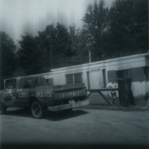 Leora Hoge with the Lynches' Trailer and Pickup Truck [Photograph]