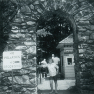 Leora Hoge under the Stone Arch at the Lobo Wolf Park Entrance [Photograph]